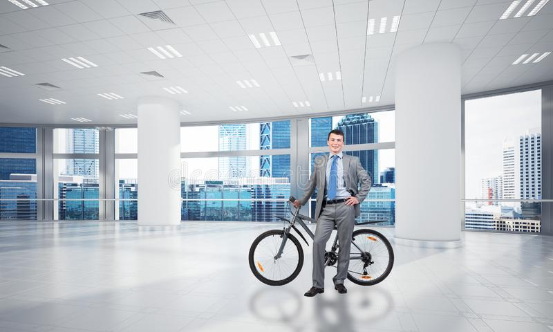 Деловой костюм молодого человека нося с велосипедом стоковые изображения