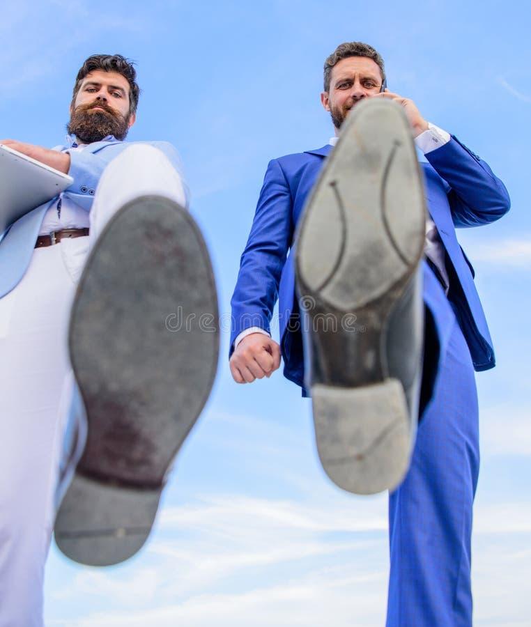 Деловой партнер занятый при телефонный звонок двигая вперед, конец ботинка ноги вверх Ломая конкурентоспособность Делать бизнесме стоковые фотографии rf