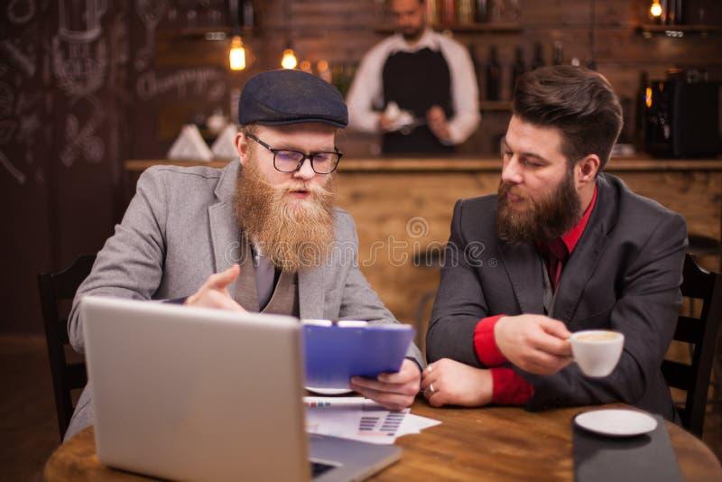 Деловой партнер 2 проверяя их последний отчет во время периода отдыха в кофейне стоковые фотографии rf