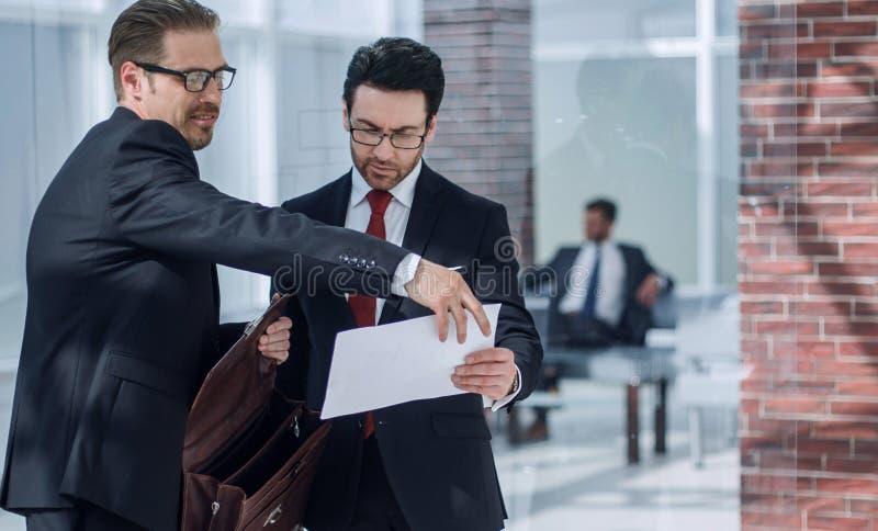 Деловые партнеры обсуждают документ стоя в лобби офиса стоковая фотография