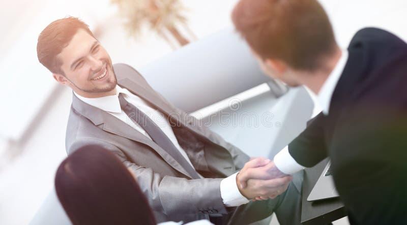 Деловые партнеры рукопожатия в лобби офиса стоковые изображения