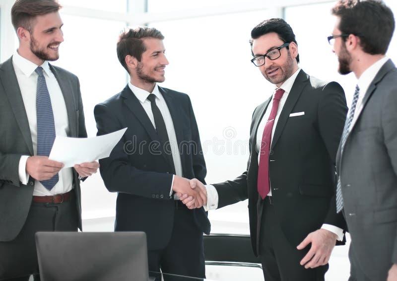 Деловые партнеры рукопожатия стоя в офисе стоковые фотографии rf