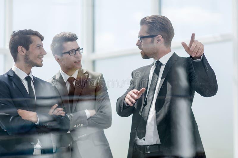 деловые партнеры стоя около окна офиса стоковое изображение rf