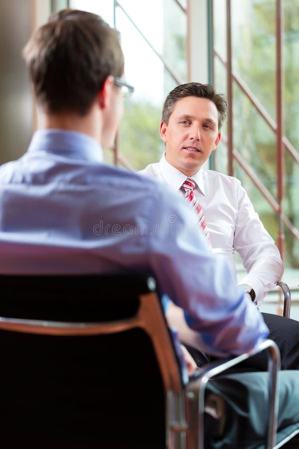 Дело - молодой человек и CEO в собеседовании для приема на работу стоковое фото