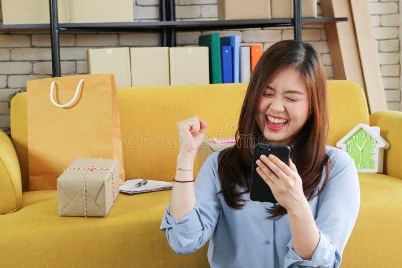 Дело начинает вверх азиатскую женщину счастливо с ее онлайн заказом от smartphone стоковая фотография rf