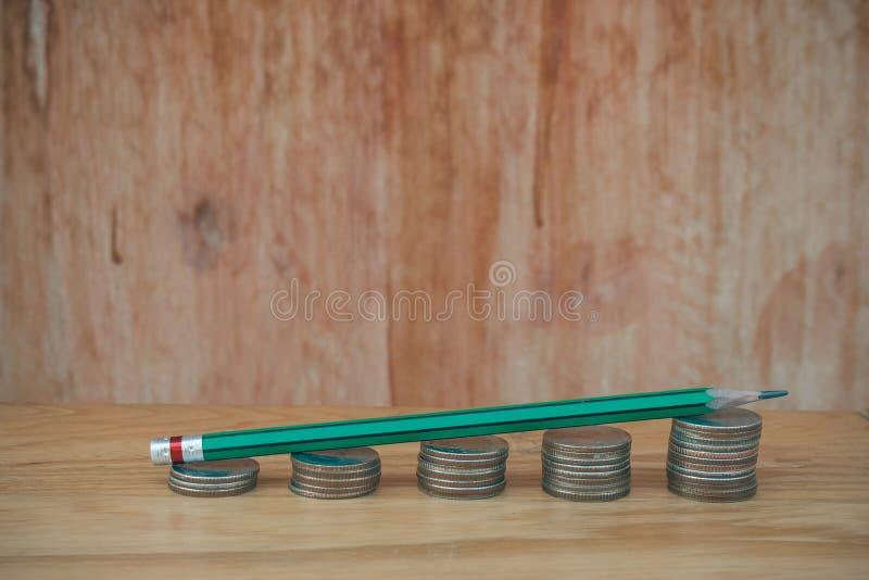 Дело творческое и концепция идеи: Используемый зеленый карандаш на стоге бата серебряных монет положенном на деревянный стол стоковые изображения rf