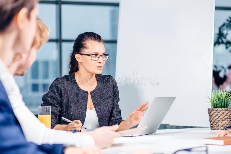 Дело, технология и концепция офиса - усмехаясь женский босс говоря к команде стоковое фото rf