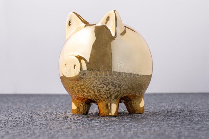 Денежный ящик свиньи золотой на черной концепции предпосылки финансовых страхования, защиты, надежного вложения капитала или банк стоковые фото