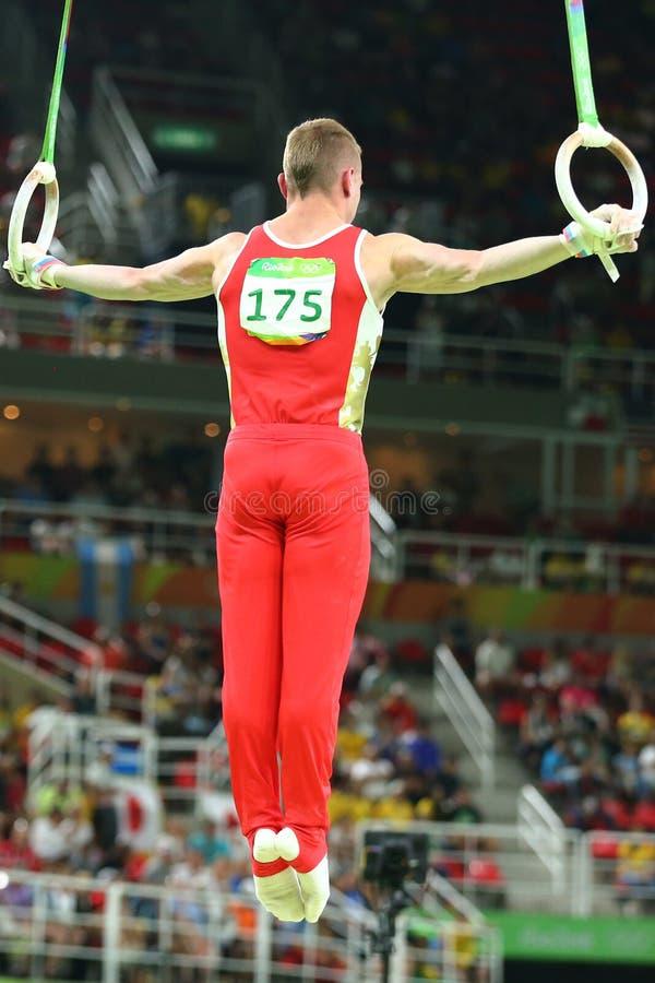 Денис Abliazin Российской Федерации состязается на кольцах ` s людей окончательных на художнической конкуренции гимнастики на Оли стоковые изображения