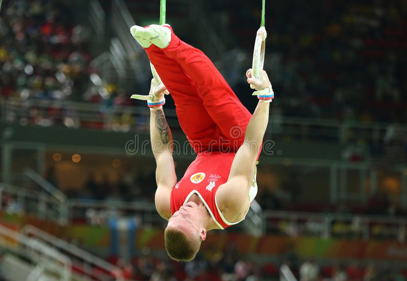 Денис Abliazin Российской Федерации состязается на кольцах ` s людей окончательных на художнической конкуренции гимнастики на Оли стоковые фото