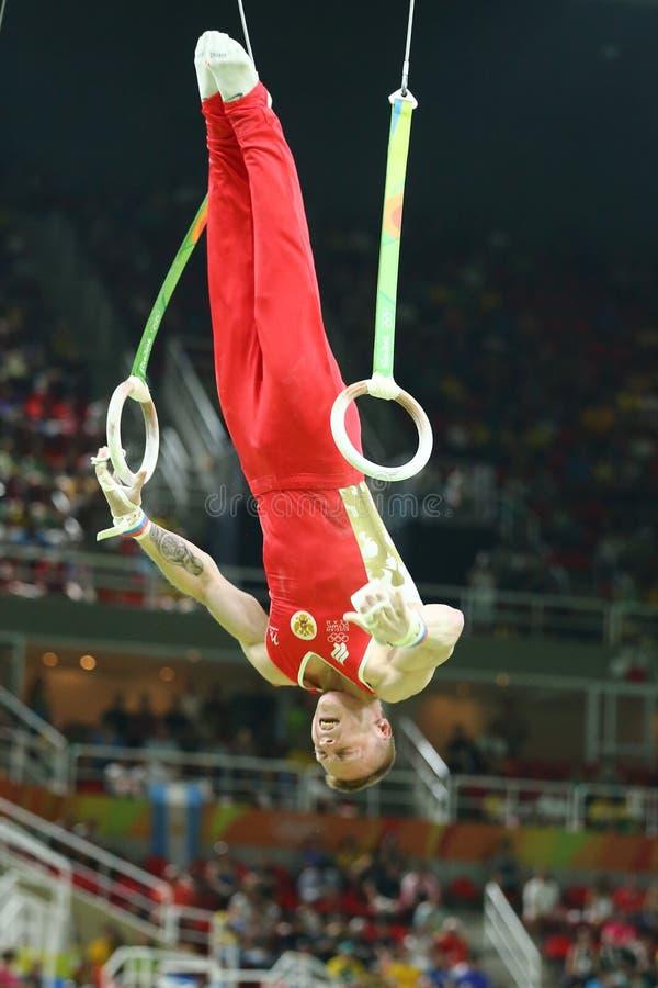 Денис Abliazin Российской Федерации состязается на кольцах ` s людей окончательных на художнической конкуренции гимнастики на Оли стоковые изображения rf