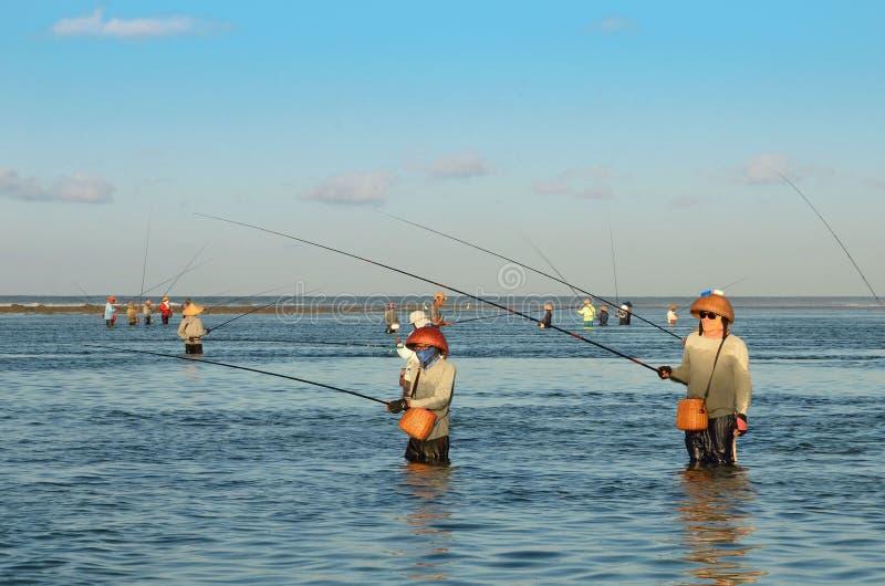 ДЕНПАСАР, ИНДОНЕЗИЯ - рыболовы 24-ое мая традиционные балийские стоя в мелководье во время отлива на пляже на Dua Nusa, Denpas стоковая фотография rf