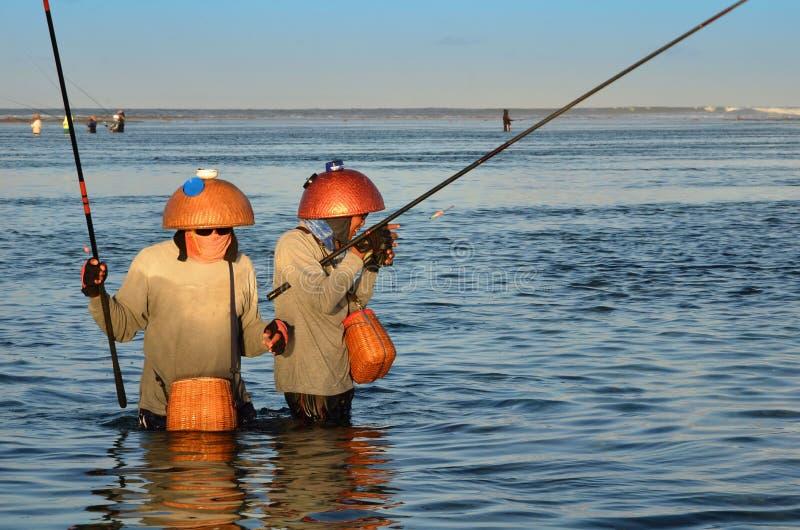 ДЕНПАСАР, ИНДОНЕЗИЯ - рыболовы 24-ое мая традиционные балийские стоя в мелководье во время отлива на пляже на Dua Nusa, Denpas стоковое фото