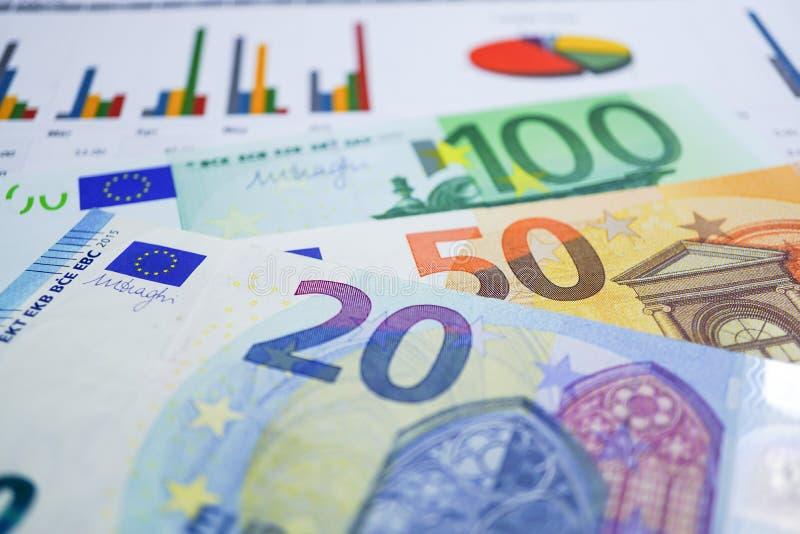 Деньги банкнот евро на миллиметровке диаграммы стоковые фото