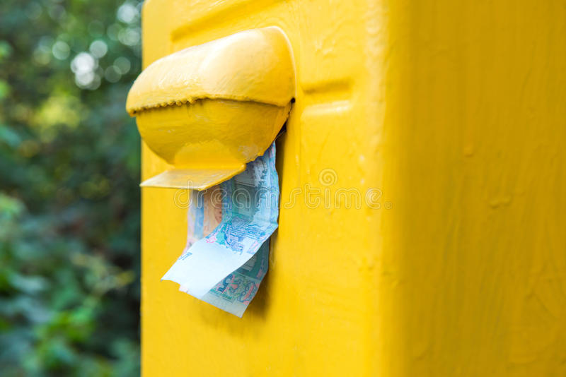 Деньги вставляя из почтового ящика стоковая фотография