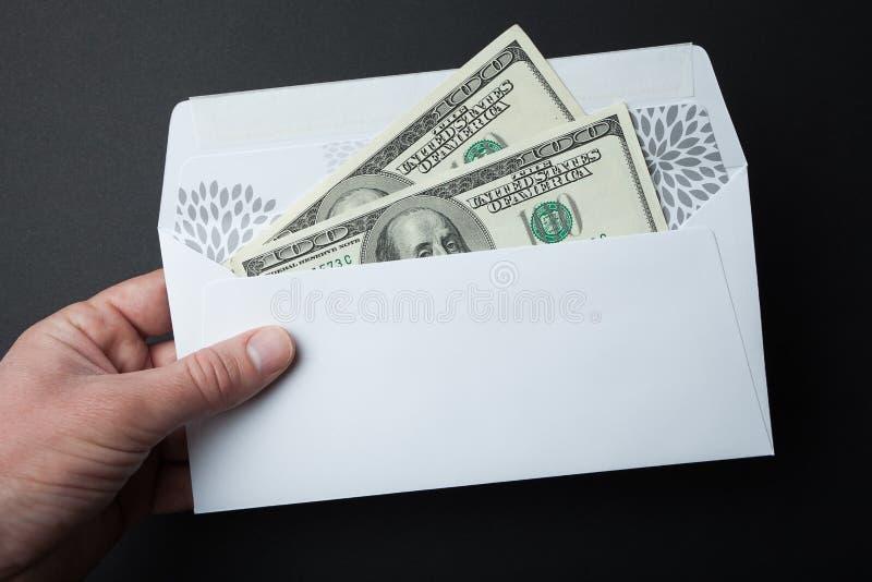 Деньги в конверте на черной предпосылке 100 долларовых банкнот стоковая фотография
