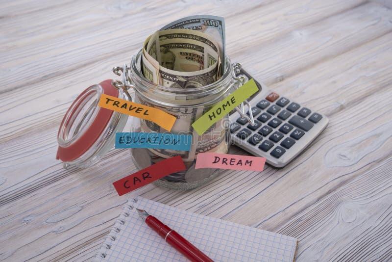 Деньги в стекле для перемещения, дома, автомобиля, образования, мечты, спасения и выхода на пенсию, сохраняют концепцию денег с стоковые изображения rf