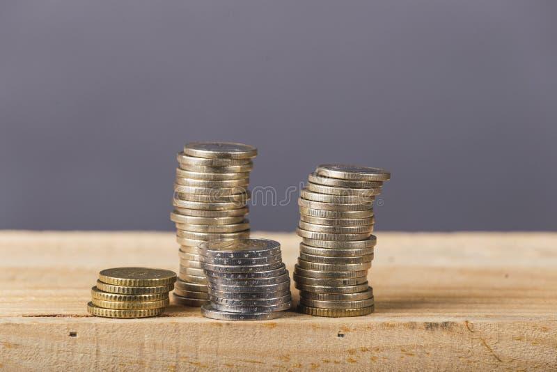 Деньги евро, валюта Монетки евро штабелируют на серой предпосылке над древесиной стоковая фотография