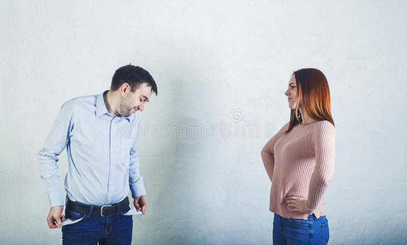 Деньги женщины требуя от ее супруга который показывает пустые карманы стоковое изображение rf