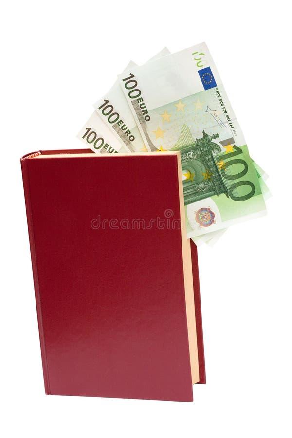 деньги изолированные книгой стоковое фото