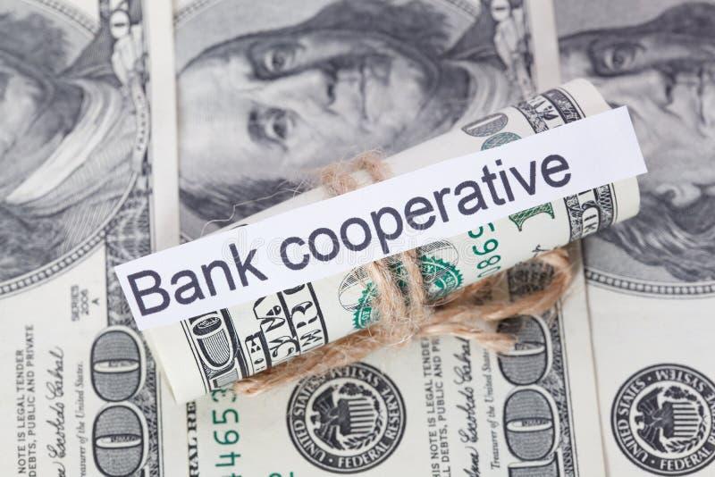 Деньги и идея дела, долларовые банкноты связали с веревочкой, со знаком - кооперативом банка стоковая фотография