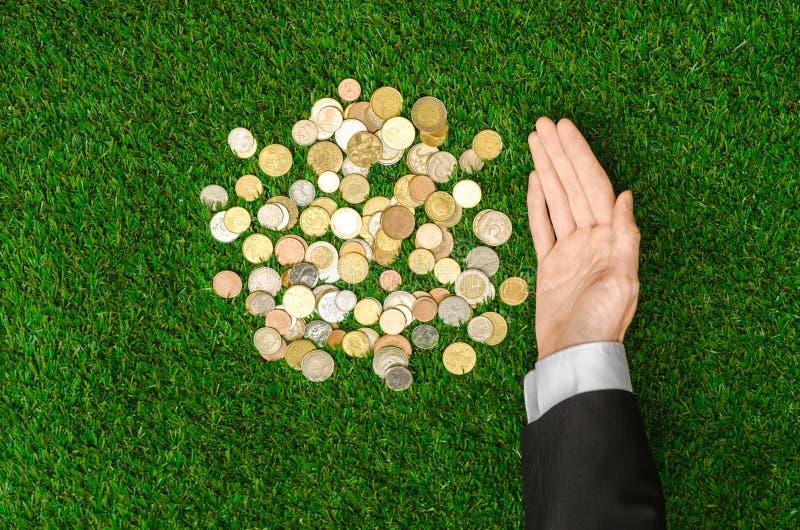 Деньги и тема финансов: Монетки денег и человеческая рука в черном показе костюма показывать на предпосылке взгляд сверху зеленой стоковое изображение