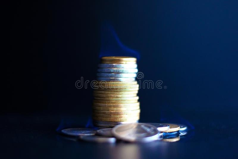 Деньги концепции бегут вне быстро, монетки металла горят с голубым пламенем стоковые фото