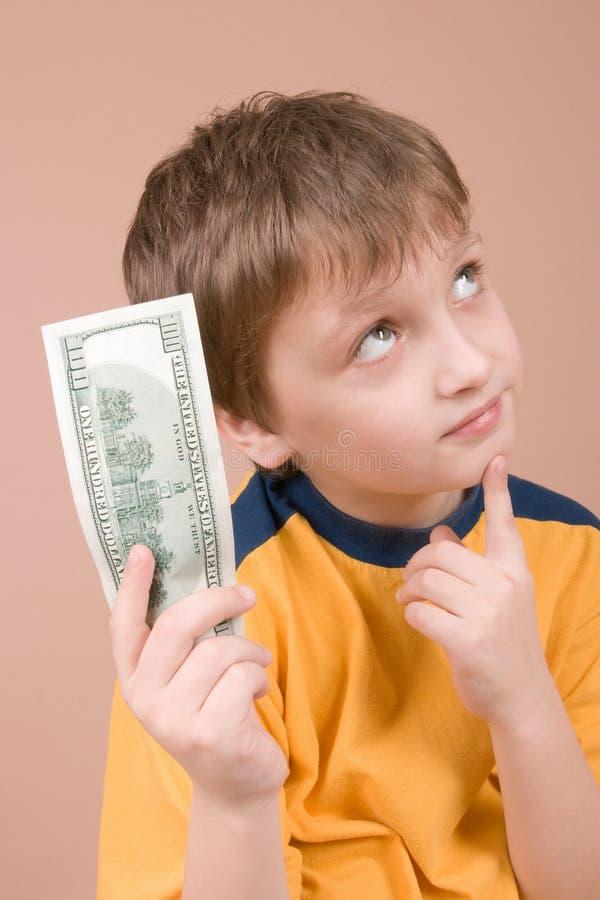 деньги мальчика показывая детенышей стоковая фотография