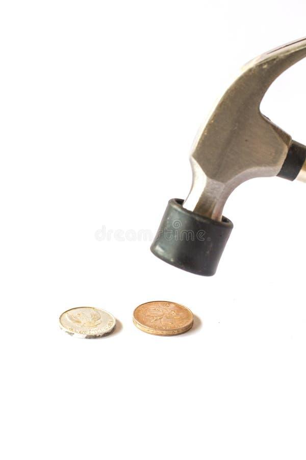 Деньги монетки удара Хаммера на белой предпосылке стоковое изображение