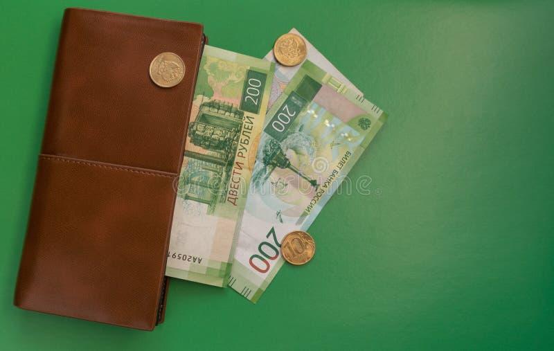 деньги на зеленой предпосылке с бумажником стоковая фотография