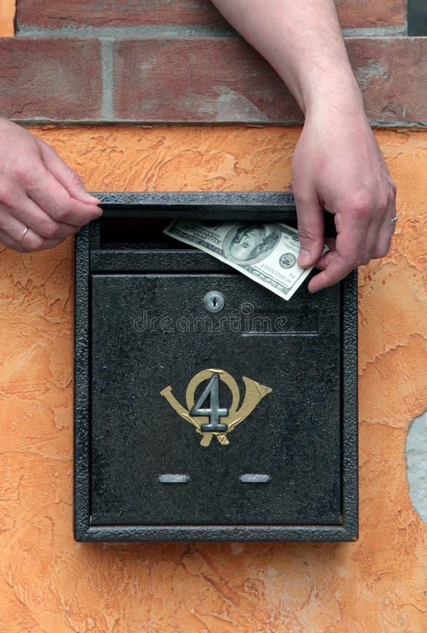 деньги почтового ящика рук кладут стоковое изображение