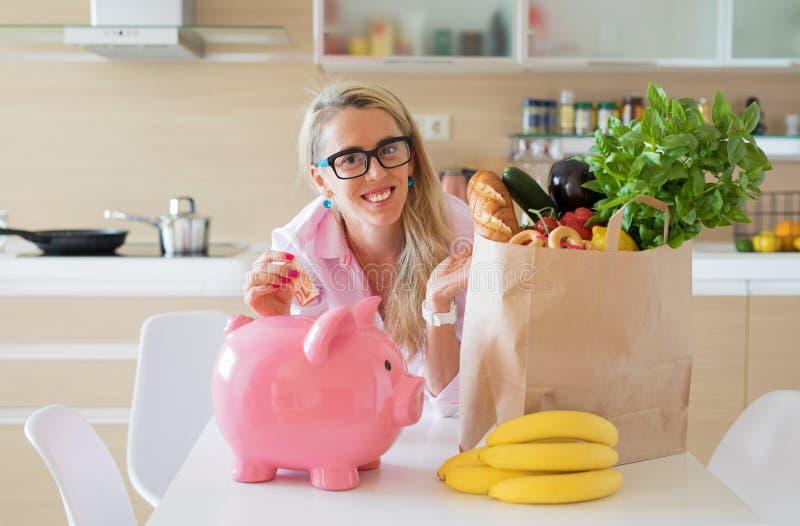 Деньги сбережений домохозяйки умными покупками бакалей стоковая фотография