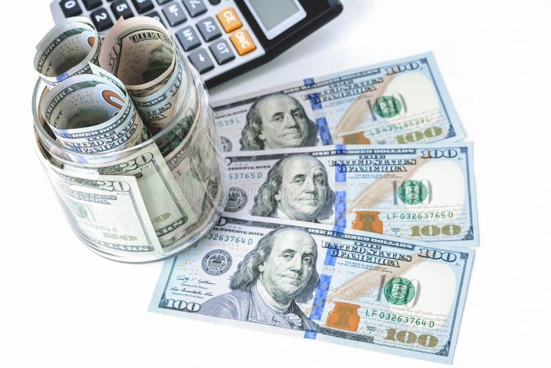 Деньги, счеты доллара США, с калькулятором на белой таблице стоковые изображения