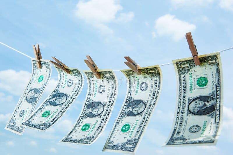 Деньги с деревянной зажимкой для белья на бельевой веревке стоковые изображения rf