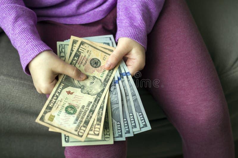 Деньги, финансы и концепция людей - усмехаясь маленькая девочка с долларом получает деньги наличными стоковые фотографии rf