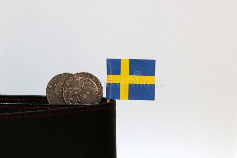 Деньги шведских кронов 2 монеток и мини ручка флага Швеции на черном бумажнике с белой предпосылкой стоковое фото