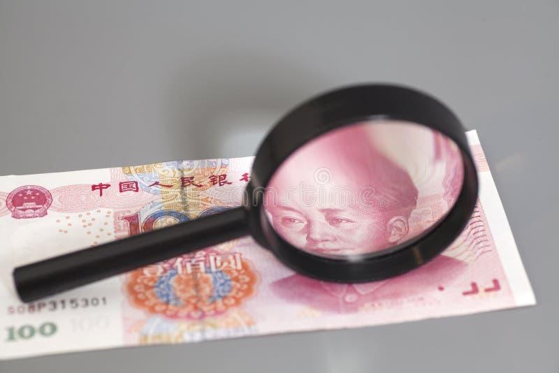 Деньги юаней китайские с стеклом увеличителя стоковые фото