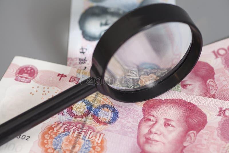 Деньги юаней китайские с стеклом увеличителя стоковая фотография rf