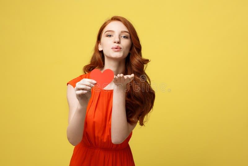 День валентинки, концепция любови и роман: Счастливая девушка дуя поцелуй Молодая женщина в ярких вскользь одеждах с бумагой стоковая фотография