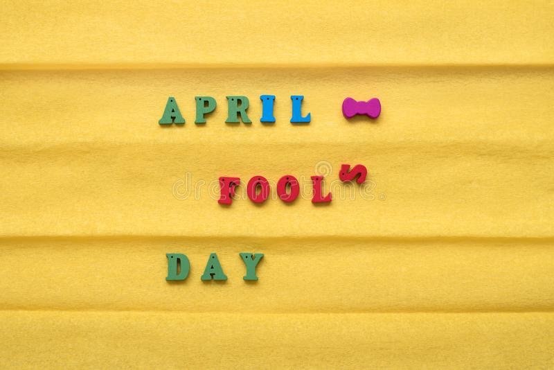 День дня дурачка, надпись от пестротканых писем на желтой бумажной предпосылке стоковые изображения