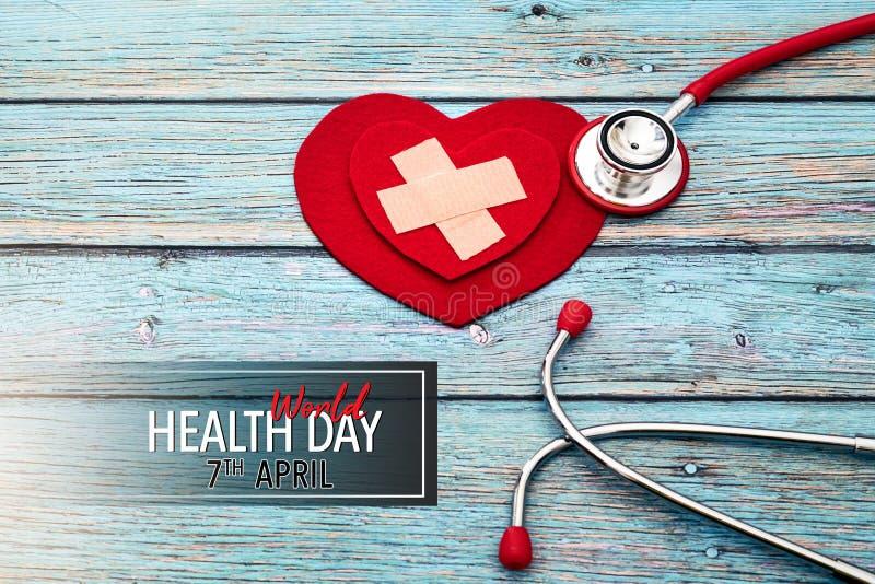 День здоровья мира, здравоохранение и медицинская концепция, красный стетоскоп и красное сердце на голубой деревянной предпосылке стоковые изображения rf