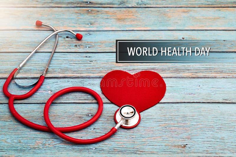 День здоровья мира, здравоохранение и медицинская концепция, красный стетоскоп и красное сердце на голубой деревянной предпосылке стоковые фото