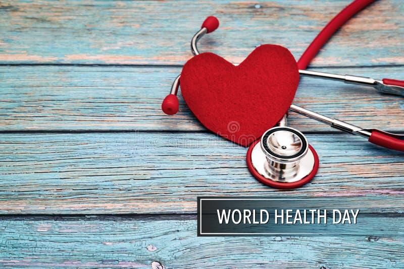 День здоровья мира, здравоохранение и медицинская концепция, красный стетоскоп и красное сердце на голубой деревянной предпосылке стоковая фотография