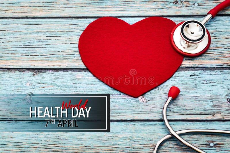 День здоровья мира, здравоохранение и медицинская концепция, красный стетоскоп и красное сердце на голубой деревянной предпосылке стоковое фото rf