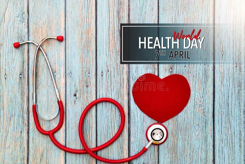 День здоровья мира, здравоохранение и медицинская концепция, красный стетоскоп и красное сердце на голубой деревянной предпосылке стоковое фото