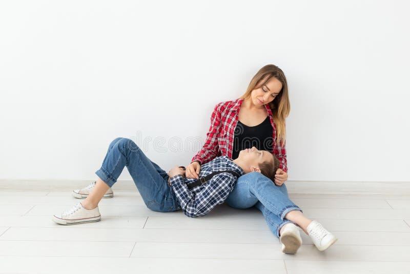 День матерей, дети и концепция семьи - милый предназначенный для подростков мальчик с его молодой матерью дома стоковые фотографии rf