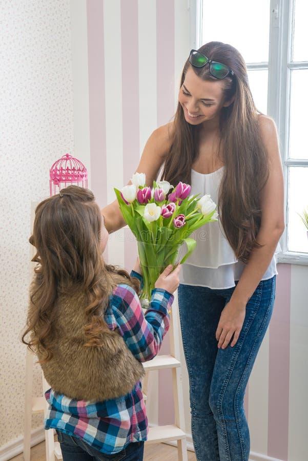 День матери - девушка дает ее маме большой букет тюльпанов, касаясь стоковая фотография rf