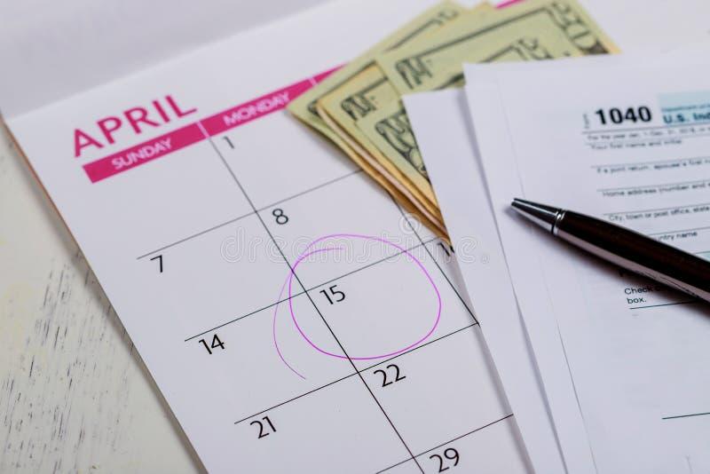 День налога, доллары и день 1040 налога показа налоговой формы подоходного налога формы для календаря в апреле со словами стоковое фото rf