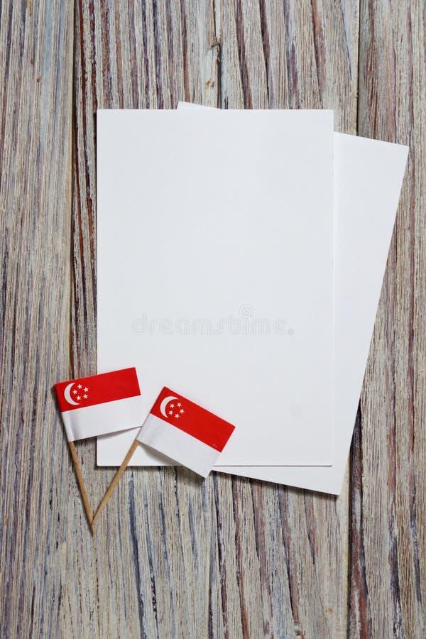 День независимости Сингапура 9-ое августа концепция свободы, независимости и патриотизма мини флаги с листами белой бумаги дальше стоковая фотография rf