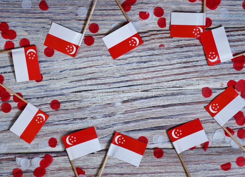 День независимости Сингапура 9-ое августа концепция свободы, независимости и патриотизма мини флаги с confetti на деревянном стоковые фотографии rf